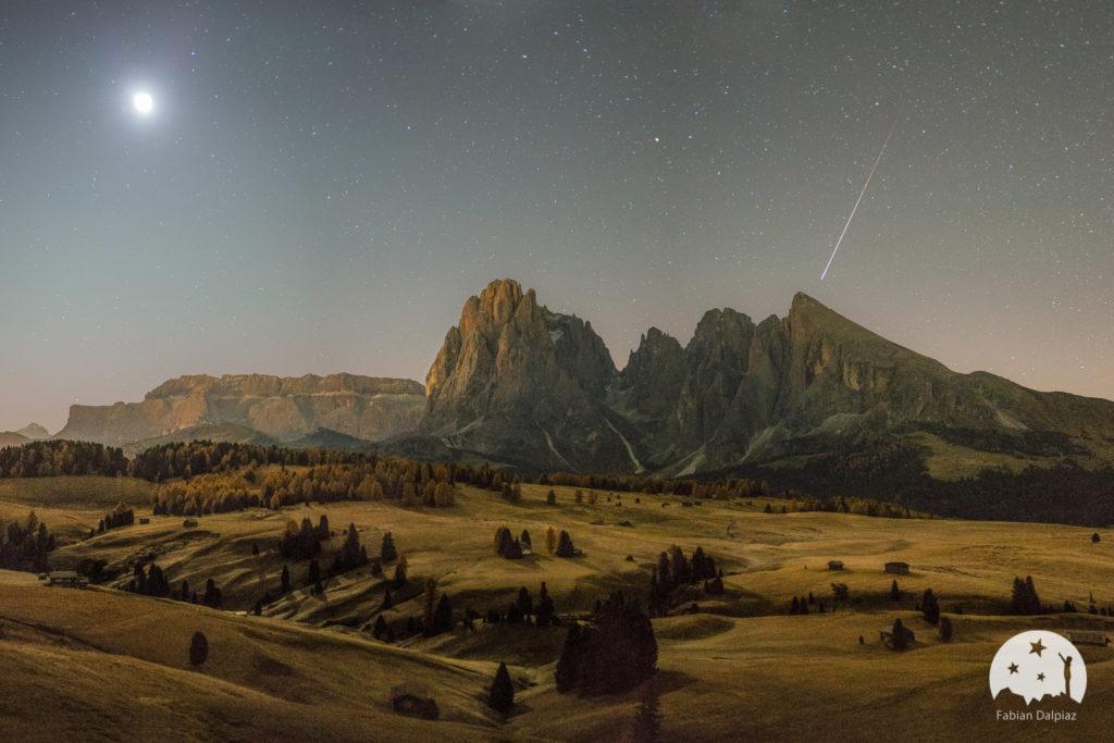Seiser Alm mit Blick auf den Sellastock. Platt- und Langkofel sind zu sehen, links am Himmel der Mond, rechts eine Sternschnuppe